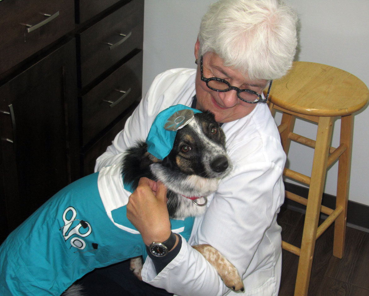 Dr. Claudia holding her dog who is in a Halloween costume
